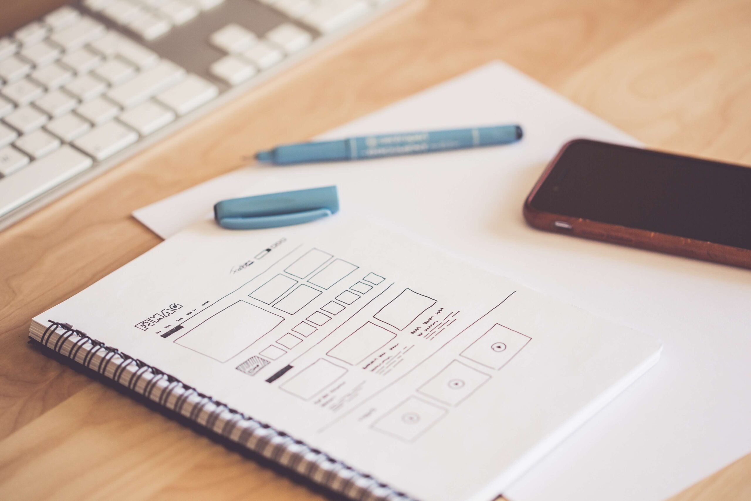 A white notebook with sketches of a new website design that includes the Rule of Thirds.