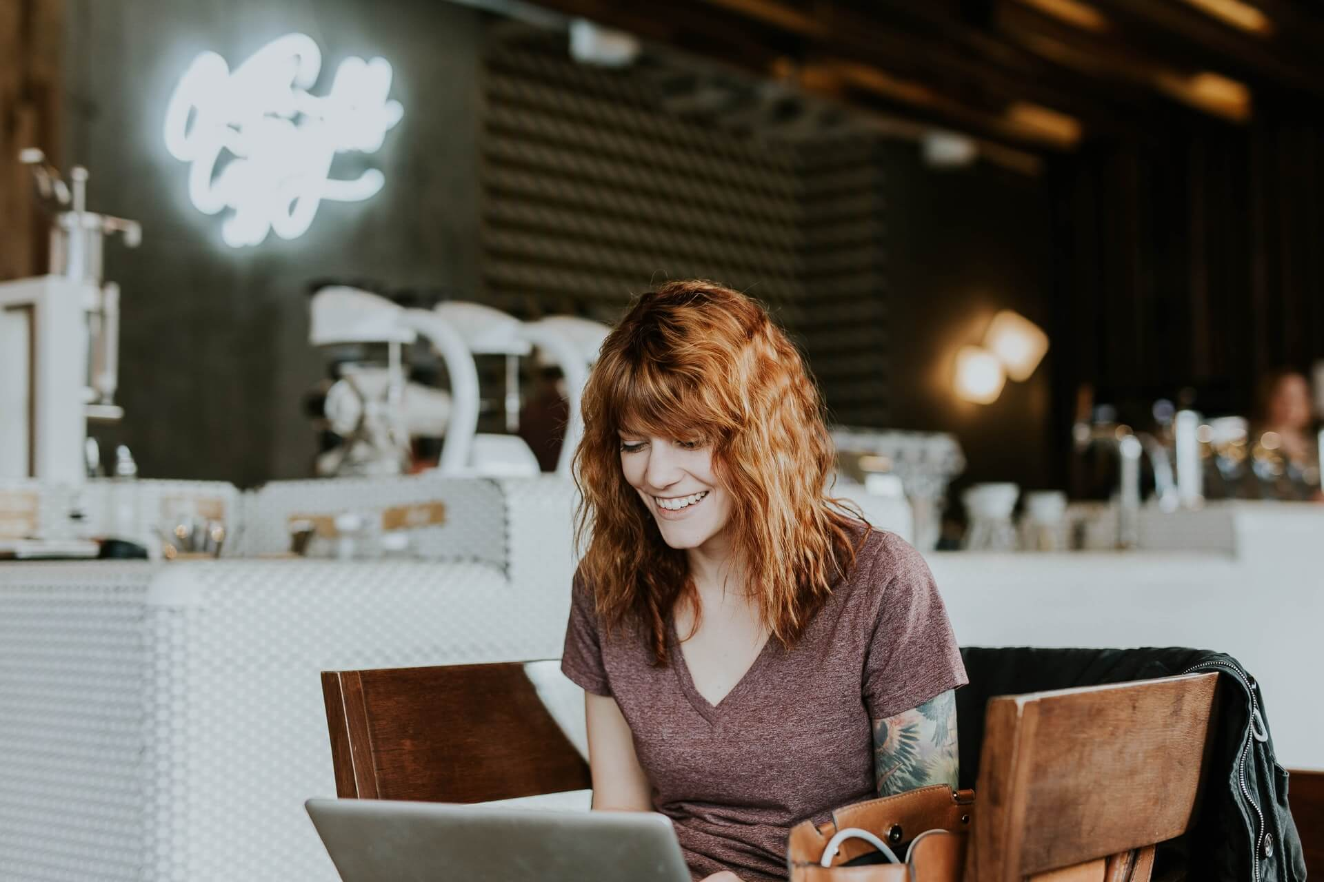 Female digital marketing professional works remotely in a coffee shop and manages automated bidding strategies.