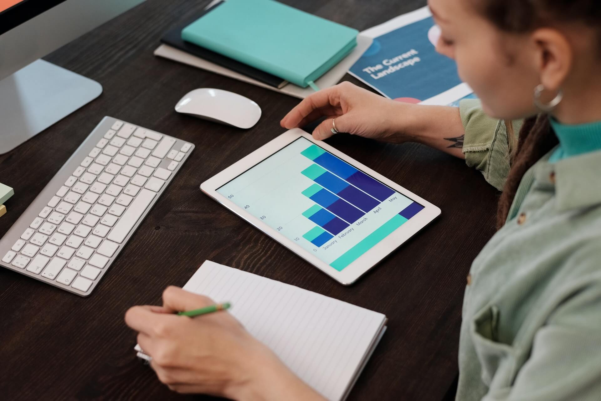 A female digital marketing professional analyzes paid advertising data and charts for future advertising strategies.