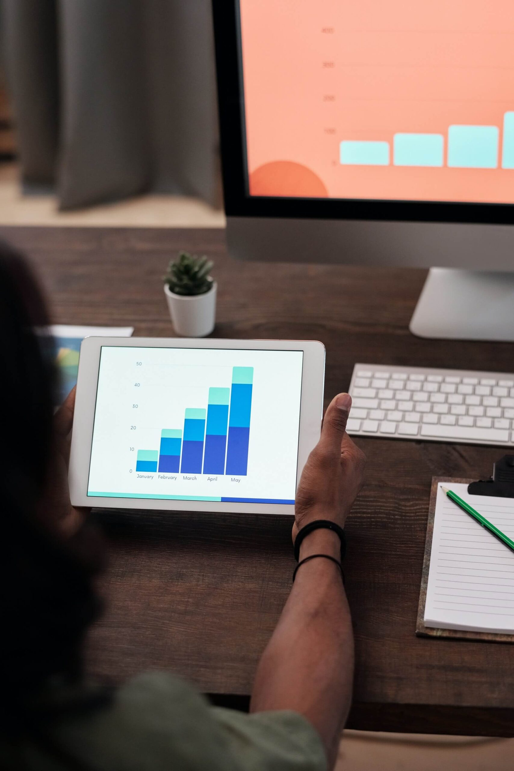 A digital marketing professional analyzes data on a blue bar graph to gather information and PPC takeaways for 2021.