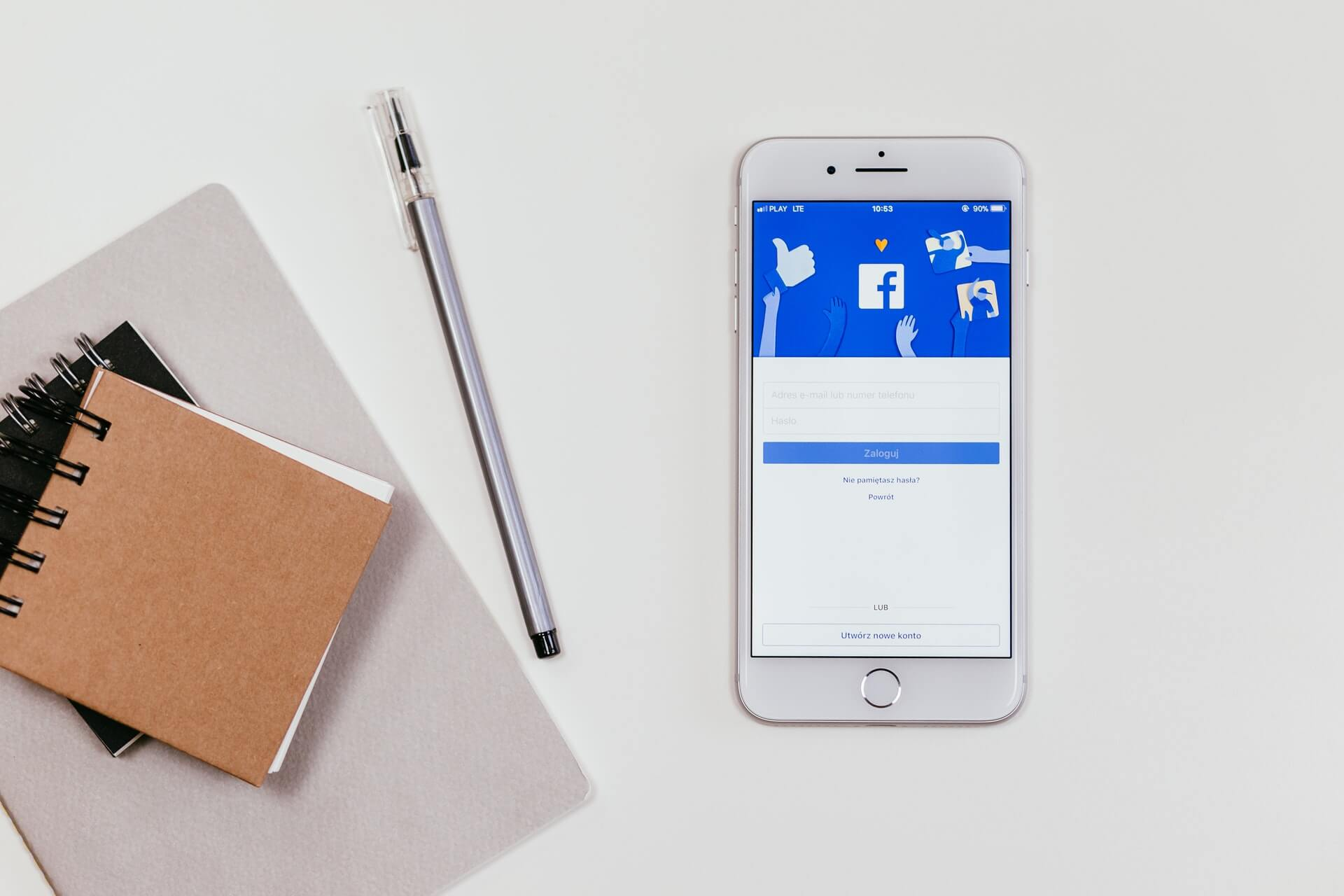 A white iPhone with the Facebook login shown on the screen after downloading the new iOS 14 update.